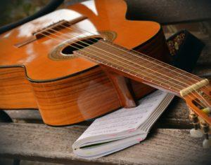 Gitarr ligger på ett nothäfte och de ligger på en bänk